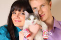 Fortunate young husband and wife hold cat Royalty Free Stock Photo