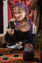 Fortune teller dealing tarot cards pretty female gypsy with Stock Image