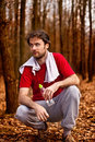 Forty years old runner man drinking water having rest jogging workout autumn forest Stock Photos
