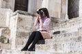 Fotógrafo da jovem mulher que toma as fotos que sentam no as escadas de pedra Imagens de Stock Royalty Free
