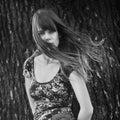 Foto van vrouw het stellen dichtbij een boom met winderig haar Stock Foto's