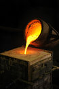 Foundry - molten metal poured from ladle into moul Stock Images