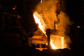 Foundry Worker Watching Hot Liquid Metal Flow Royalty Free Stock Photo