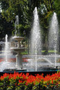 Fountain in city park with red flowers Stock Photos