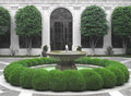Fountain in a courtyard water the middle of an enclosed with green shrubs Royalty Free Stock Photo