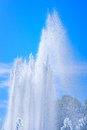 Fountain jet at sunny day and water spray against blue sky and distant threes Royalty Free Stock Photos