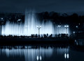 Fountain night people silhouettes urban scene in a park in moscow russia by evening illuminated by streetlamps with reflected on Stock Image
