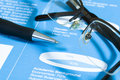 Fountain pen and glasses on stock chart. Royalty Free Stock Photo