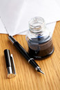 Fountain pen and inkwell on desk Royalty Free Stock Photo