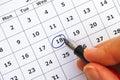 Fountain pen in woman hand marking day on calendar
