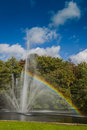 A fountain in a pond with a rainbow multiple fountainheads bathed mid day bright light making beautifull Stock Photo