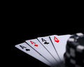 Four aces on black table with chips Stock Images