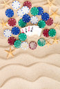 Four aces with poker chips on beach sand surrounded by and scattered starfish golden a decorative wavy pattern and copyspace Royalty Free Stock Image