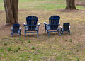 Four adirondack chairs in forest Royalty Free Stock Photo