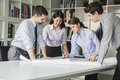 Four architects standing and planning around a table while looking down at blueprint Stock Photo