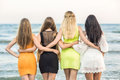Four attractive young women standing on a sea background. Pretty ladies` backs in bright dresses. Girls posing and Royalty Free Stock Photo