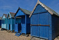 Four beach huts blue on the seafront Stock Images