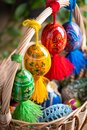 Four beautiful hand painted Easter eggs, made of wood in a brown wicker basket – decoration of a holiday table during celebratio Royalty Free Stock Photo