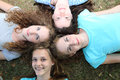 Four beautiful teenage friends female lying on their backs with their heads close together smiling up as they enjoy their summer Stock Photos
