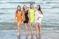 Four beautiful young girls stand in the background of a sea shore, full-lengths. Charming young women in multi-colored Royalty Free Stock Photo