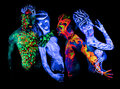 Four body art glowing in ultraviolet light Stock Photo
