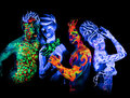 Four body art glowing in ultraviolet light Stock Images