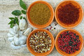 Four bowls with saffron, pepper, ras en hanout, fresh mint and Royalty Free Stock Photo