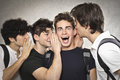 Four boys three boy telling secrets to and amazed other one Royalty Free Stock Images