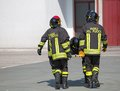 Four brave firefighters carry a fellow firefighter with the medical stretcher Stock Images