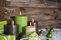 Four burning apple green christmas candles on wooden background. Royalty Free Stock Photo