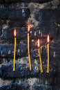 Four burning candles on old sooty blackened stone wall Royalty Free Stock Photo