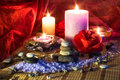 Four candles camellias little stones salt massage Stock Photo