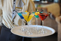 Four colored cocktails on a tray in the hands of the waiter. Yellow, blue, green, red. Decorated with a lemon slice Royalty Free Stock Photo