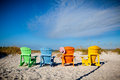 Four colorful adirondack chairs face the dunes and the sea off florida Stock Photography