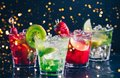 Four colorful tasty alcoholic cocktails in a row at the bar stand.. Festive holiday bokeh Royalty Free Stock Photo