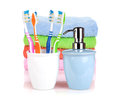 Four colorful toothbrushes, liquid soap and towels Royalty Free Stock Photos