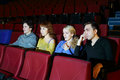 Four concentrated people watch movie in movie theater focus on right girl Royalty Free Stock Photo