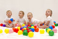 Four cute funny babies sitting on the white blanket and playing colorful balls. Infant party.