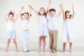 Four cute little girls and one boy hold on hands up Stock Photos