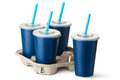 Four dark blue takeout cups with a cup holder standing on white Stock Image
