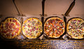 Four different delicious pizzas in boxes Royalty Free Stock Photo