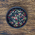Four different kinds of peppercorns in clay bowl on wooden background, square format, top view