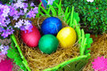Four easter eggs in a natural straw colorful with flowers close up Stock Photo