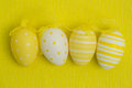 Four easter eggs row against yellow background Stock Photos