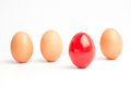 Four eggs row one red one standing out white background Stock Photos