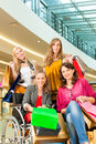 Four female friends shopping in a mall with wheelchair bags having fun while stores the background one woman is sitting Royalty Free Stock Images
