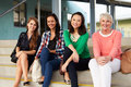 Four female teachers sitting on steps at entrance of school Royalty Free Stock Photo