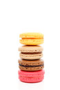 Four fluffy baked macaroon biscuits delicious mouthwatering of various flavours standing tall in a tower stack isolated on white Stock Image