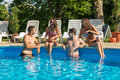 Four friends having fun in the swimming pool Royalty Free Stock Image