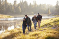Four friends having fun walking beside a lake Royalty Free Stock Photo